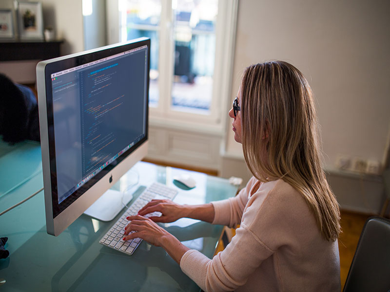 Woman coding at a desktop map computer