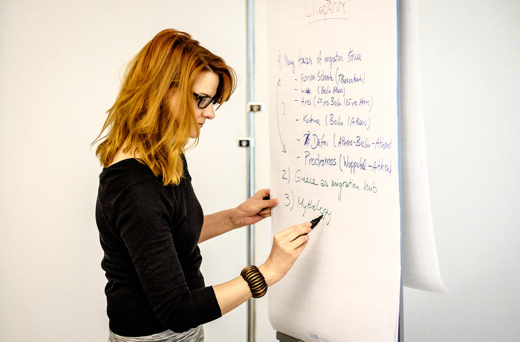 Young woman writing on a flip chart