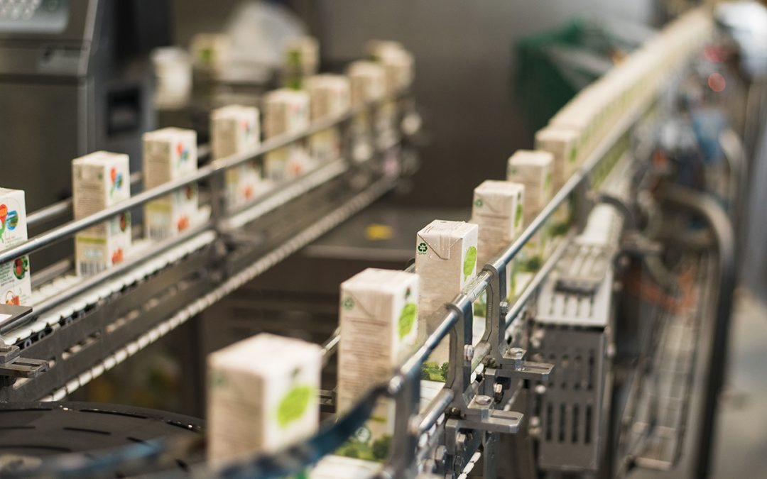 Cartons of juice moving along a production line in a factory